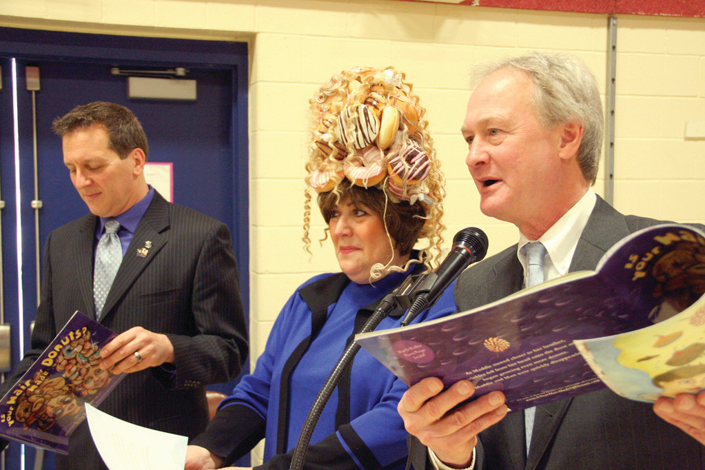 OH SO GOOEY: Eva Marie Mancuso, chair of the state Board of Education, wears the donut hat as Gov. Chafee reads from Feldman�s book and Rep. Frank Ferri awaits his turn recently at John Wickes School.