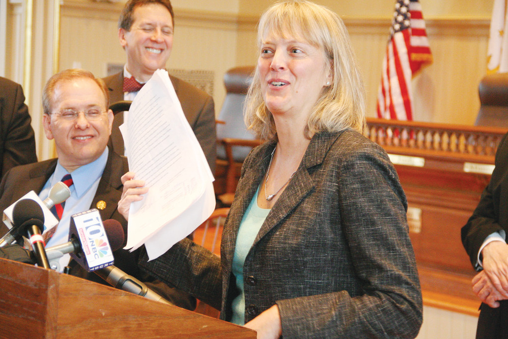 IT'S OFFICIAL: DEM Director Janet Coit waves the agreement selling the state 82 acres of Rocky Point at Thursday's closing on the property.  Looking on are Congressman James Langevin and Rep. Frank Ferri.
