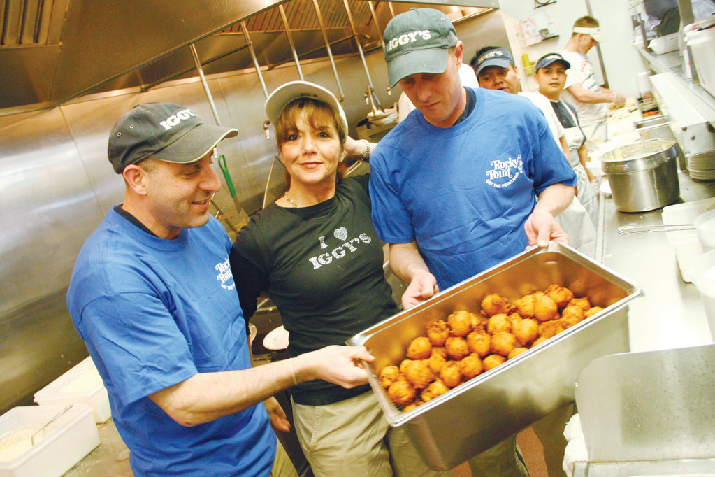 ROCKY POINT COMES TO IGGY'S: David Gravino, left, owner of Iggy's, provided clamcakes in Rocky Point bags for the historic state acquisition of 82 acres of the former park Thursday. Joining him here are Sue Gravino and Mike Clark. Clark and Garvino wore Rocky Point T-shirts for the occasion.