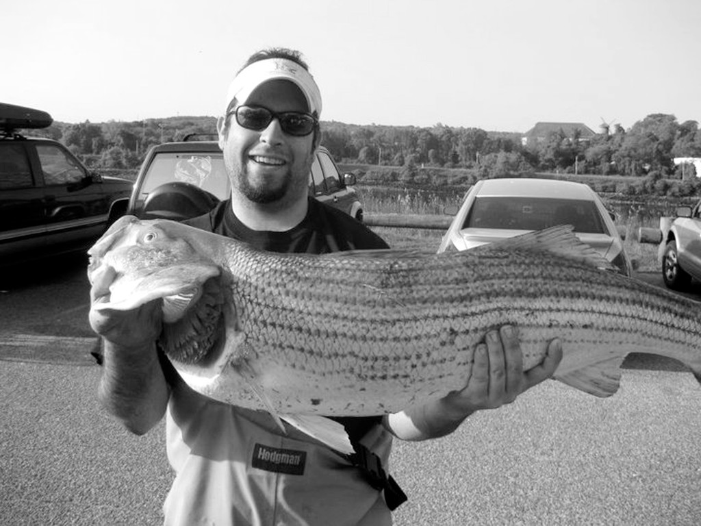 Striped bass highway:  Chris Parisi of Fish Whisper Guide Service with a striped bass he caught on the Cape Cod Canal.  Chris said the Canal is like a river that changes direction, filled with a lot of current, structure and bait… perfect for striped bass fishing.