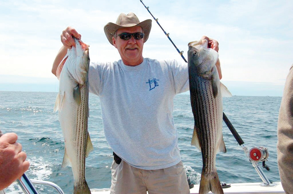 WHAT HE LOVES DOING:  Warwick's Richard Hittinger displays two stripers. Hittinger was the spark plug behind the idea of assessing the impact of recreational fishing on the state's economy and developing an action plan to keep it alive and growing.