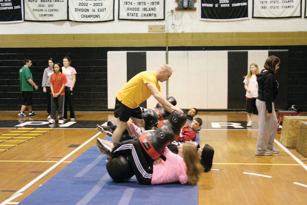 PUSHING THEIR LIMITS: Staff Sgt. Dennis Parent helps students properly complete the modified sit-up exercise that utilized a weighted punching bag.