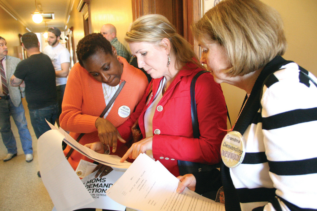 DIGGING INTO THE DETAILS: Aida Neary, Samantha Richard and Nan Heroux, all members of the Rhode Island chapter of Moms Demand Action, scan through gun control legislation Tuesday at the State House.