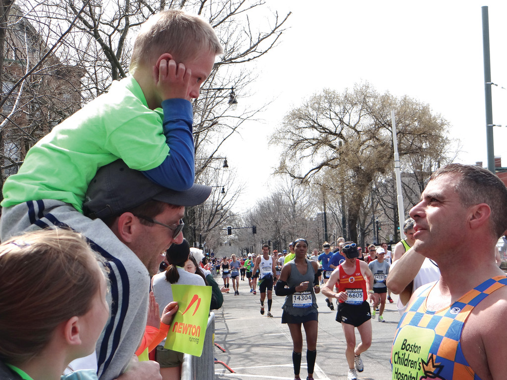 IN STRIDE: For the third year in a row, Hans Ramsden completed the Boston Marathon as part of the Boston Children's Hospital charity team on behalf of Peter, a 10-year-old boy treated at the hospital. Here, Ramsden greets Peter, who's propped on his father's shoulders, about a mile and a half from the finish line.
