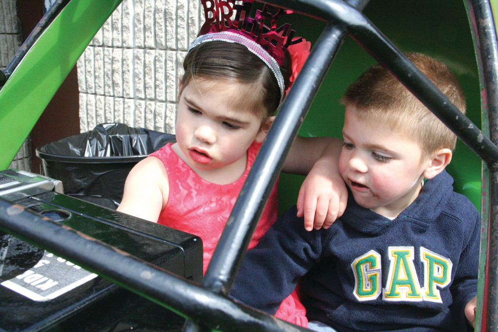 Sharing a seat of one of the playground's cars are twins Victoria and Watt Scotti who celebrated their third birthday running from one display to the next.