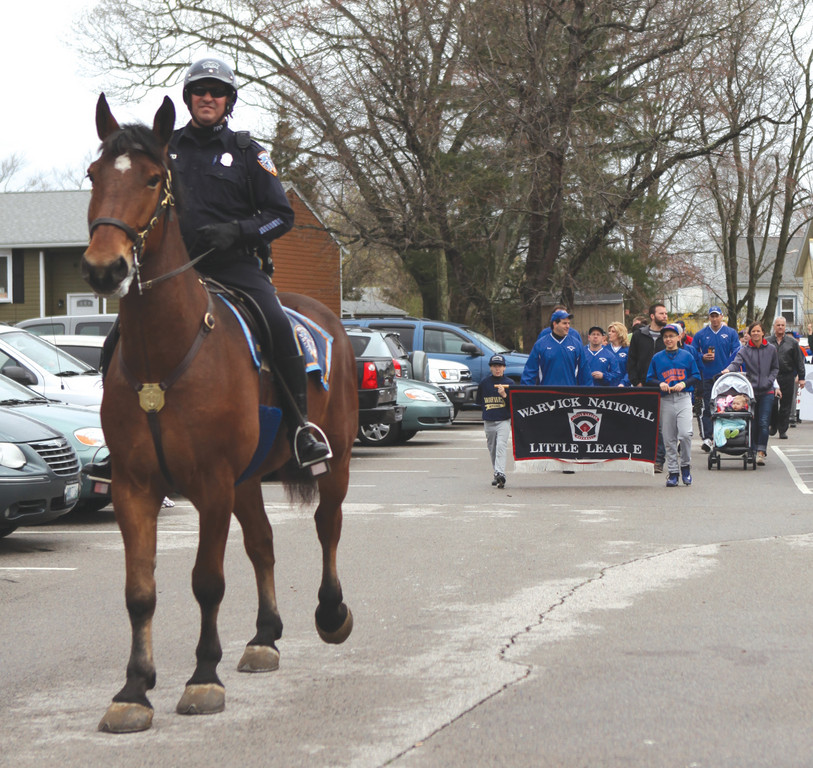 Officer Daniel Famiglietti and Cassidy lead the teams to the field.