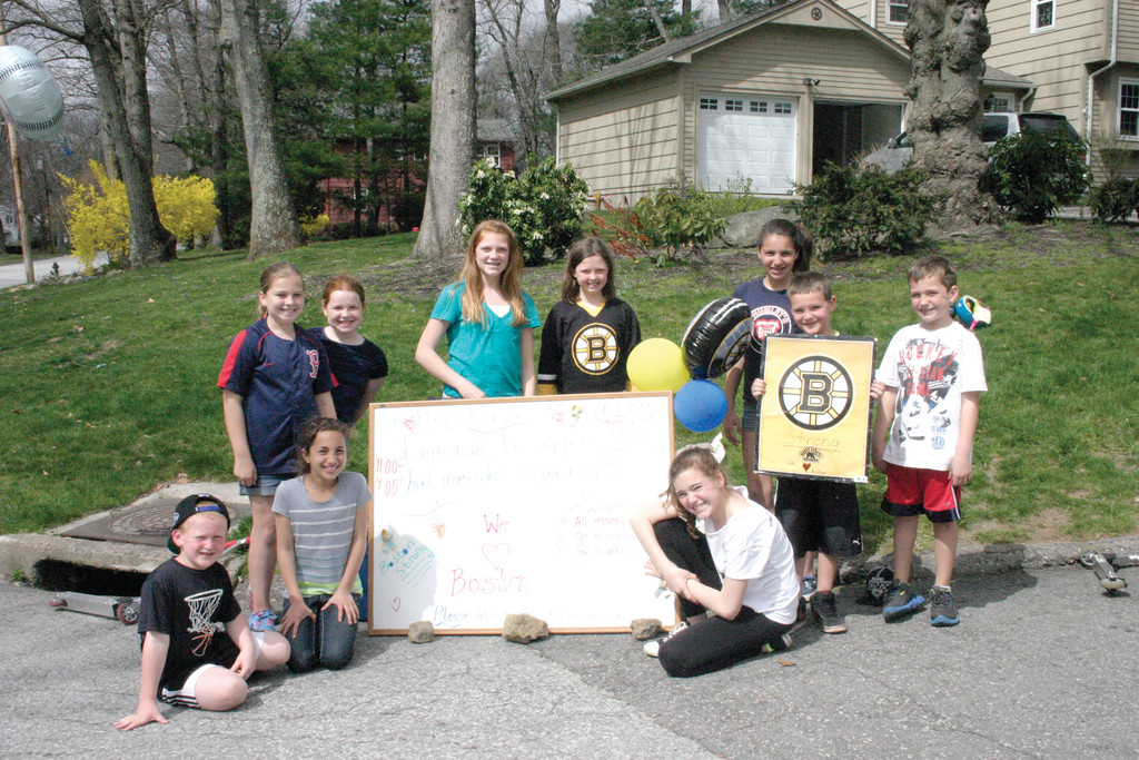 BOSTON STRONG: With the help of cousins, siblings and friends, Abigail Walsh (left, blue Red Sox jersey) and Ainsley Leahy (Boston Bruins jersey) hosted a lemonade stand at the Walsh home for three days last week, with all proceeds going to One Fund Boston