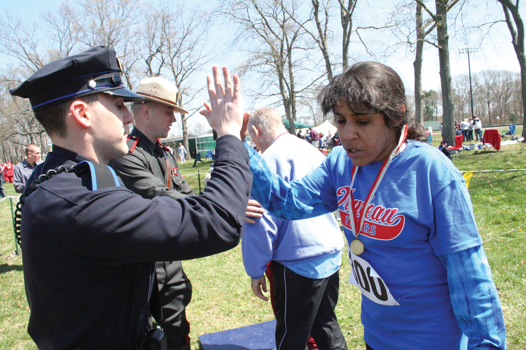 Cranston Police Officer Dave Cragin gives Gina Creque of the Trudeau Center's Tigers a high five after presenting her with a gold medal in the softball throw