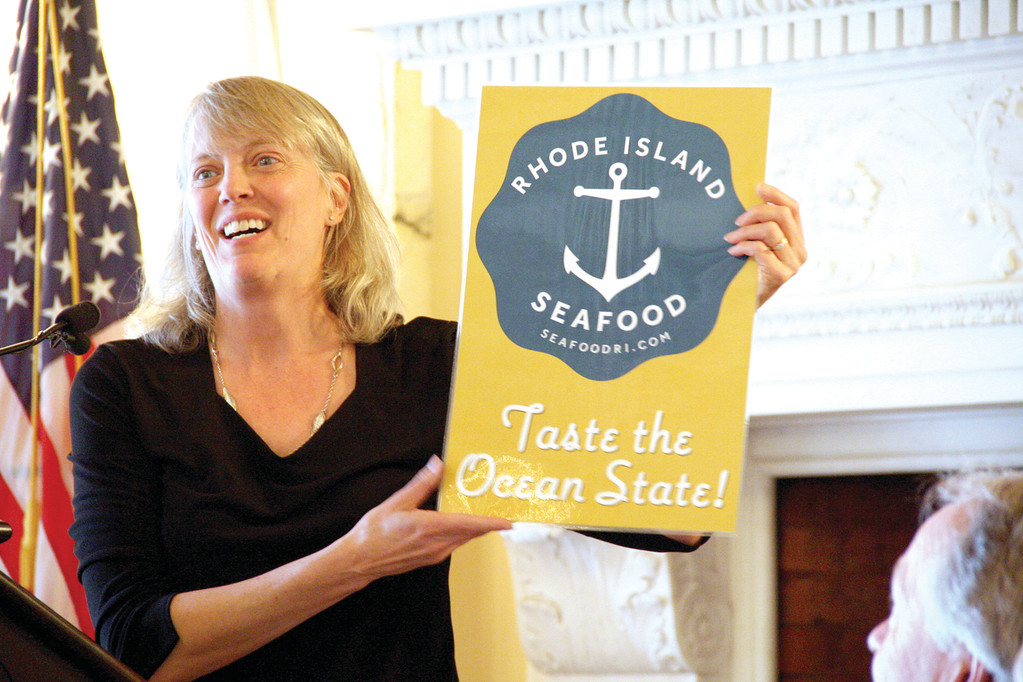 NEW LOGO: Janet Coit, DEM director, unveiled the logo to soon be seen in supermarkets and seafood shops promoting locally harvested fish and shellfish at Agriculture Day Thursday at the State House.