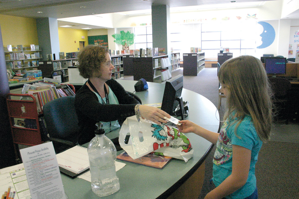 FIRST OF MANY: Maureen Mascoli, a library aide, hands Jocelyn Borkowski back her library card. Borkowski used the card for the first time during her class trip, selecting a book on mythical creatures to borrow.