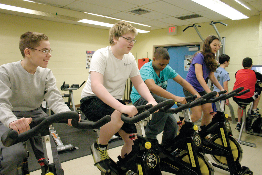 GOING FOR A SPIN: Four students take a test ride on the new spin bikes during their first class in Winman Junior High School�s new weight room.