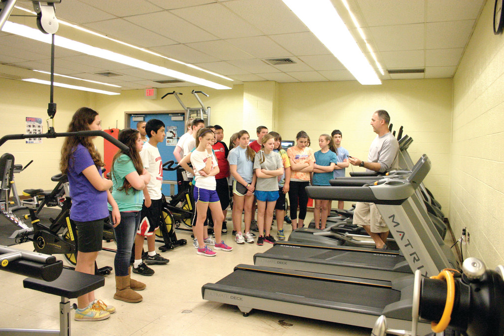 LAY OF THE LAND: A group of seventh graders listen as Physical Education teacher Rick Cirelli explains how to properly work one of the new treadmills during a walk-through of Winman's new weight room.