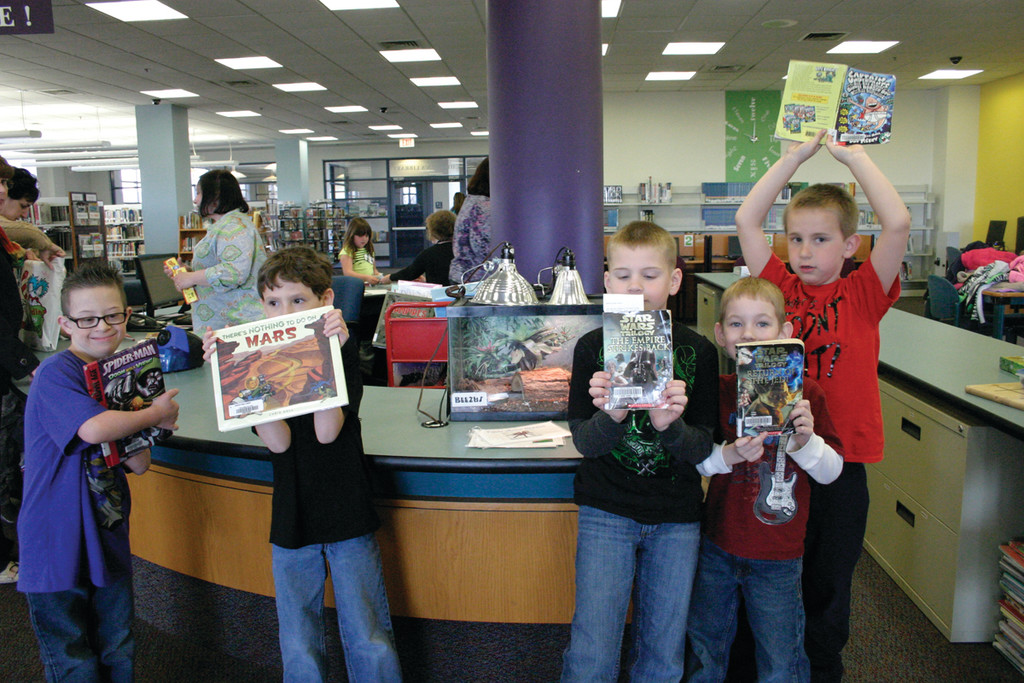 BOYS AND THEIR BOOKS: First graders Daniel Comella, Zachary Cotton, Christopher Cronin, Fernando Meo and Seth Perry show off their borrowed books while visiting Beezus, the library�s tarantula.