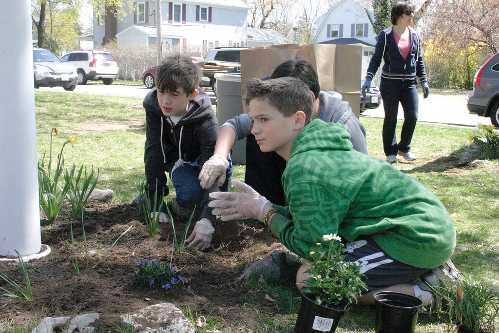 PLANTING PALS: Max Grossguth, Kyle Hadfield and Joseph Silvestre work together to plant new flowers in a bed during Greenwood's first Green Day.