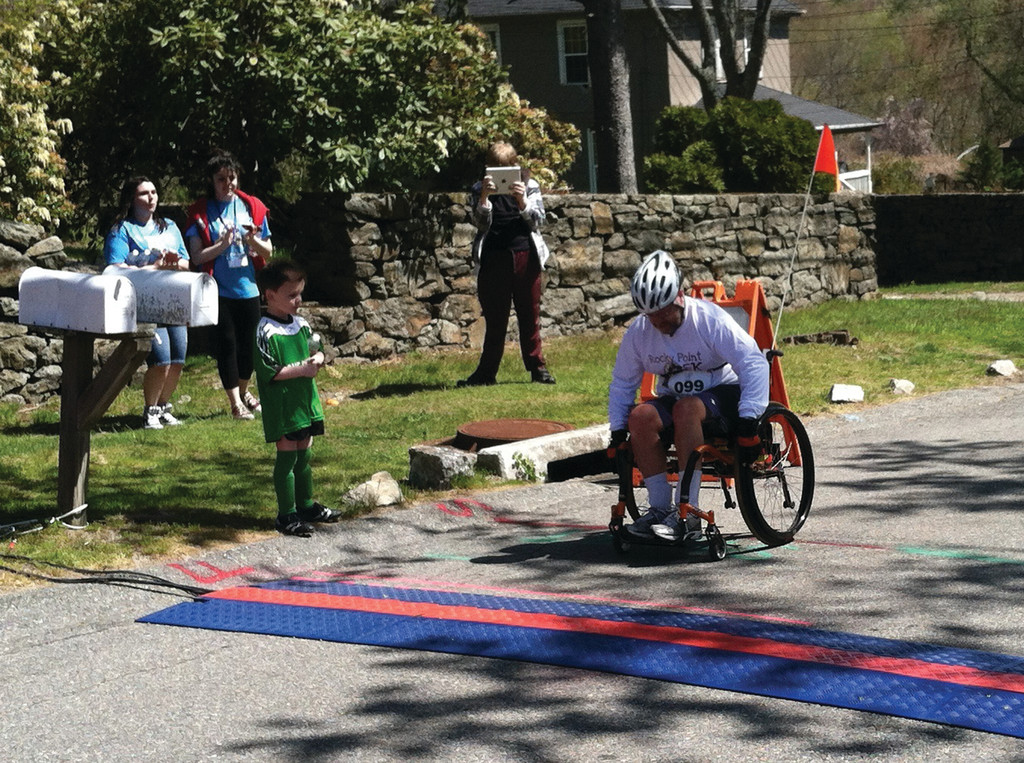 HOME STRETCH: Onlookers cheer as John Taylor of East Greenwich crosses the finish line.