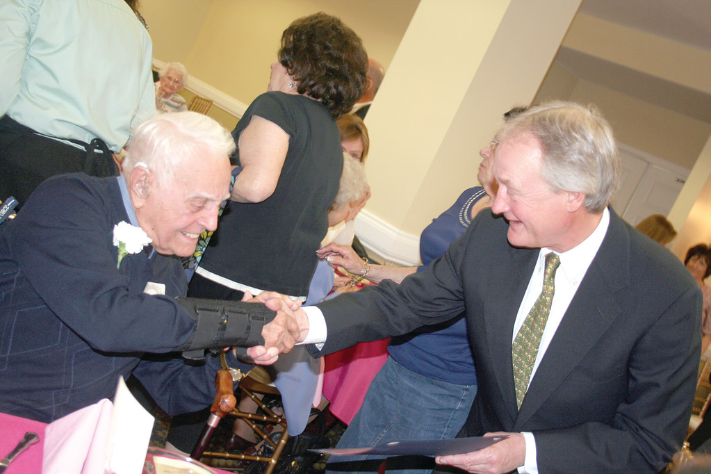 WHAT A MILESTONE: Governor Chafee congratulates Joseph Celona of North Providence who, at 105 years old, was the oldest man in attendance last Thursday.