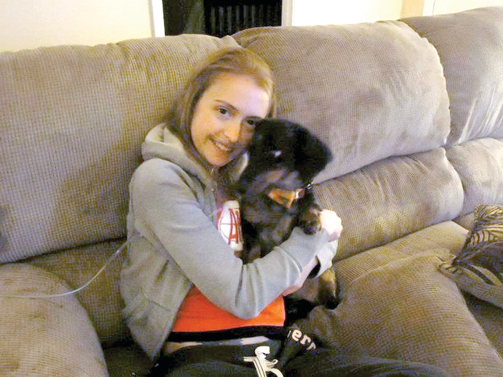 COMFORT FROM A FRIEND: Kayla Gilbert is resting comfortably with her precious pup Owen James in North Carolina following a living donor lung transplant in January. Her family is now raising money to help cover the cost of treatment and medication.