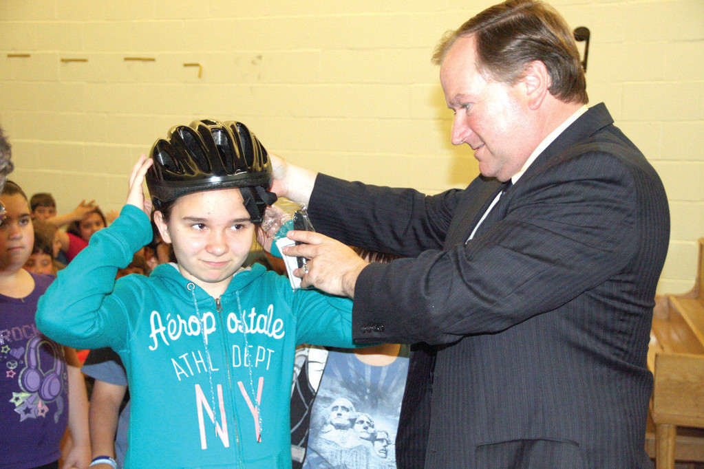 Senator Michael McCaffrey fits fifth grader Angelina Antonizio with a helmet.