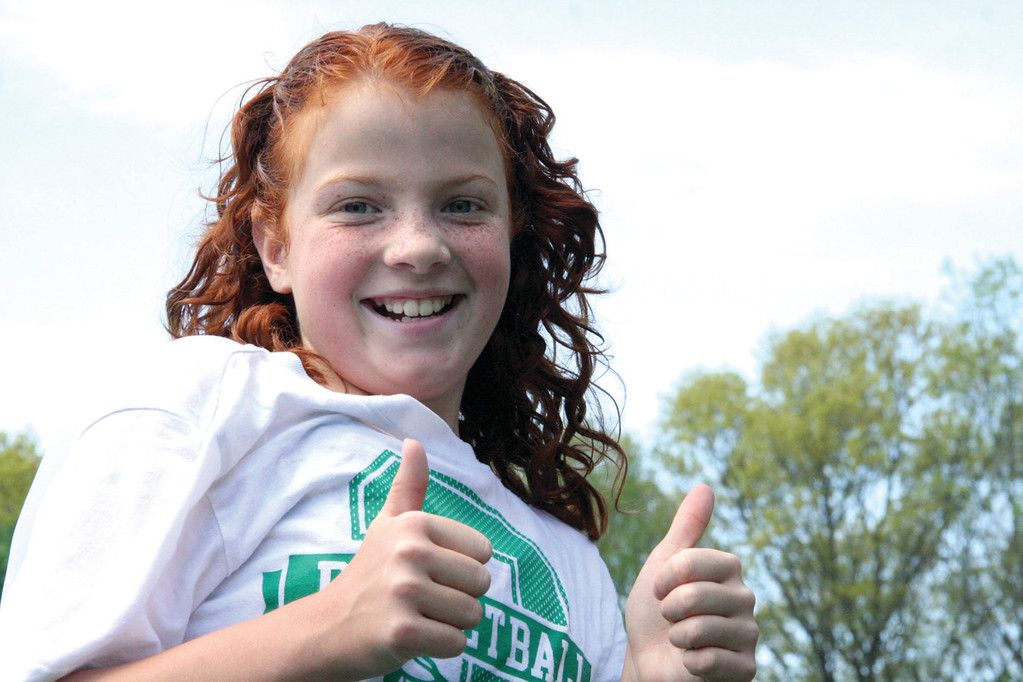 PUMPED UP: Norwood fourth grader Kelsey Burr flashes a smile and a cheer during the walk-a-thon.