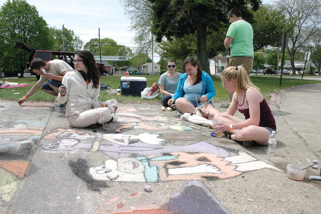 TRIBUTE TO BEDROCK: Reyna Amat, Lauren Enos, Ali Paul and Katie Evans put the finishing touches on their chalk art portrait of �The Flinstones.�