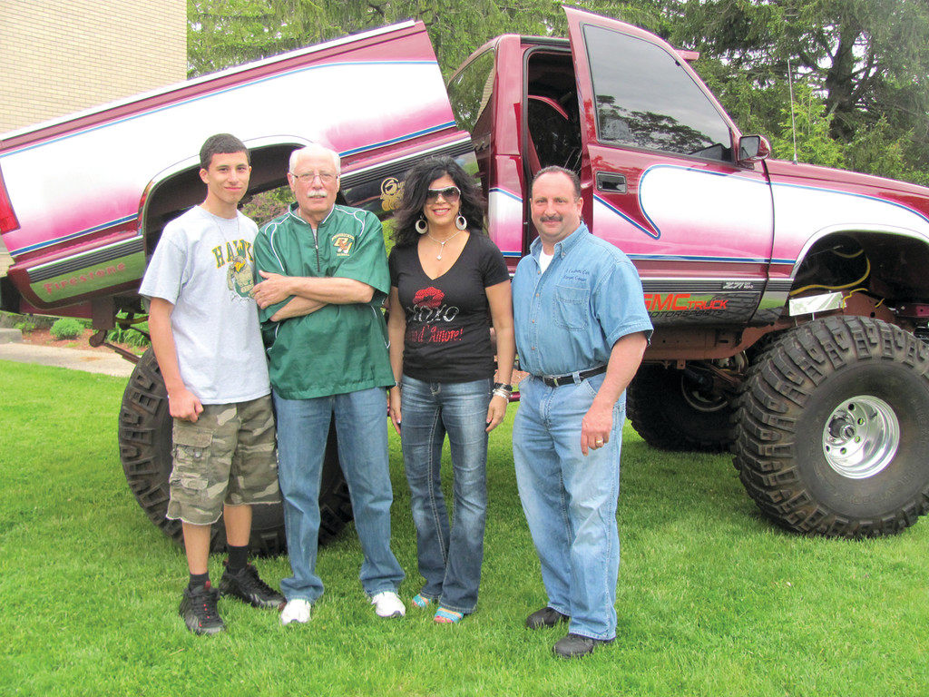 MONSTER TRUCK: Mike Benedetto (second left), chairman of the fourth annual Bishop Hendricken High School Car Show, joins the Arakelians – George III, George Jr. and his wife Gina Sabitoni-Arakelian – by the monster truck that was on display Sunday. The show raised nearly $2,000 for the school's Inner City Scholarship Fund.