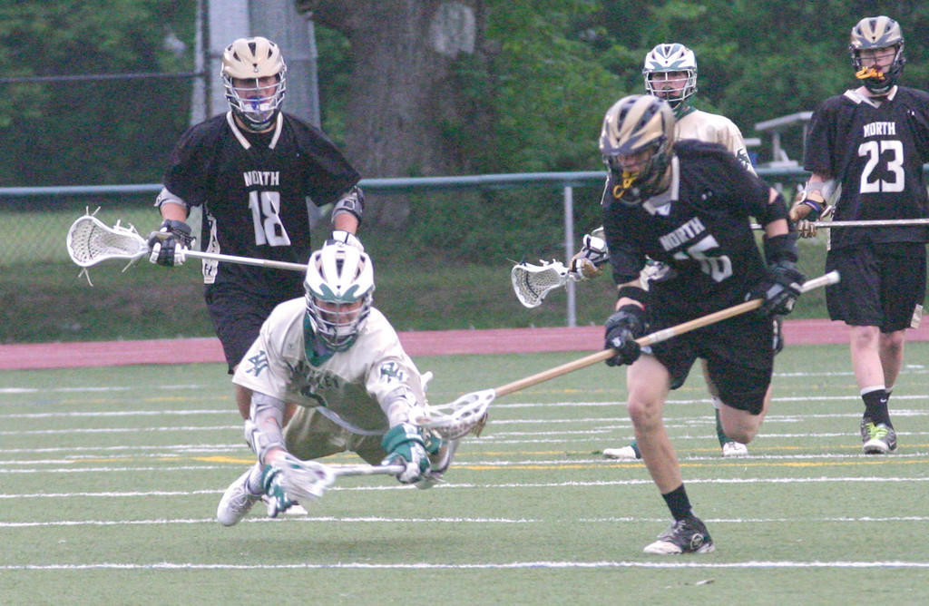 STRETCH: Hendricken's C.J. Marrinan dives for a ground ball as North Kingstown's David Poirier scoops it up.