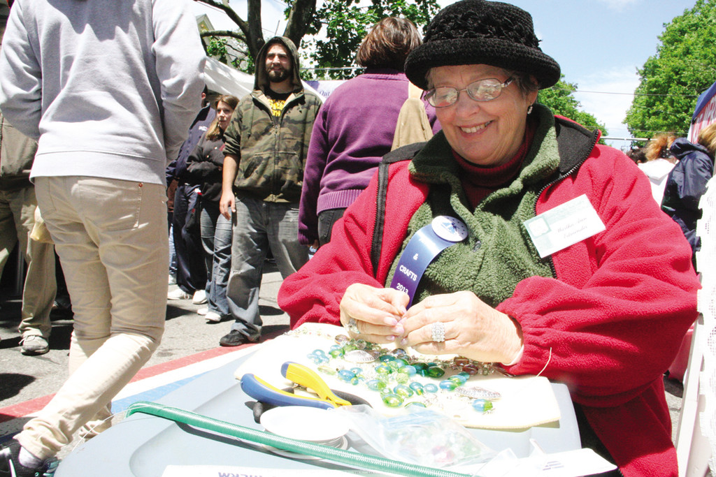 NO QUESTION IT IS HANDMADE: Martha Ann Edminster assembles necklaces while waiting for customers Sunday at the festival.