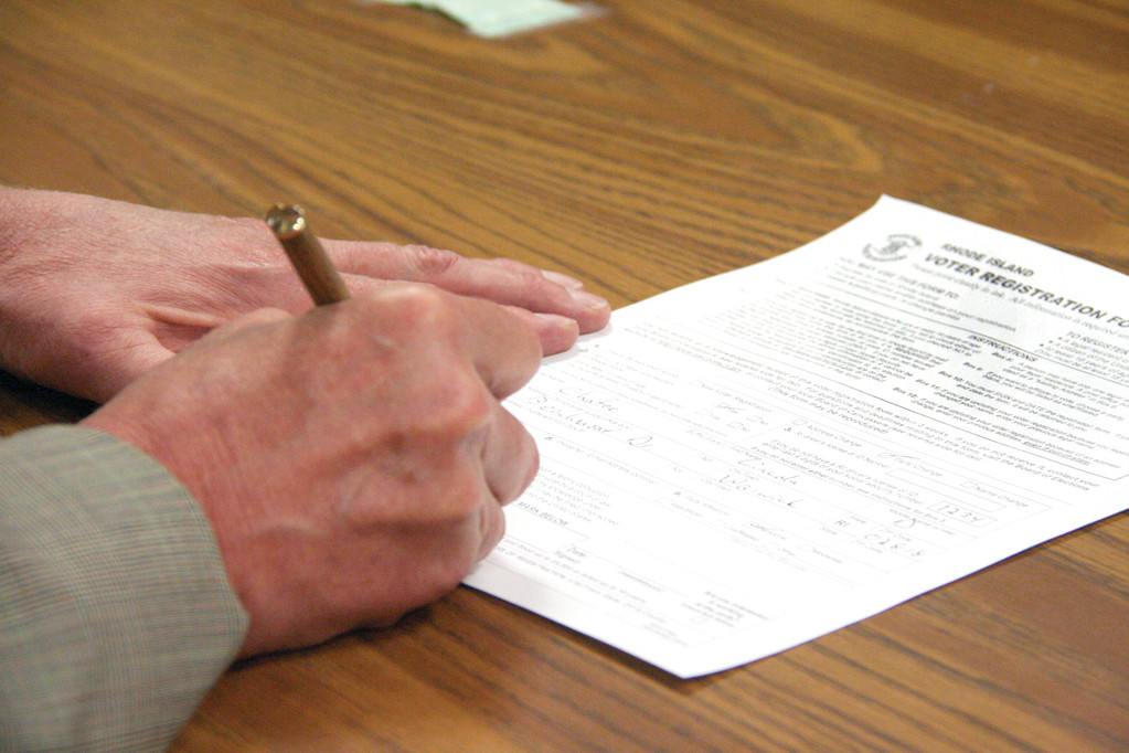 Gov. Chafee signs registration papers in the Board of Canvassers to become a Democrat.