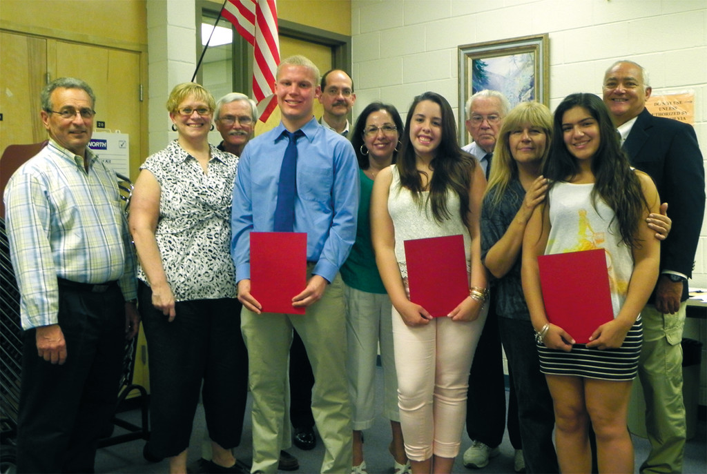 HOT SCHOLARSHIPS: Warwick seniors Brianna Florio, Chris Vanasse, and Tayla Hall are joined by their parents and members from the Cataract Scholarship Committee, including Mike Shields, Otis Wyatt, Steve Hay and Ron Caniglia, after receiving Cataract scholarships at a ceremony Thursday. The scholarships were created from proceeds of the sale of the former volunteer Cataract Fire Company in 1974 when the city took over operation.
