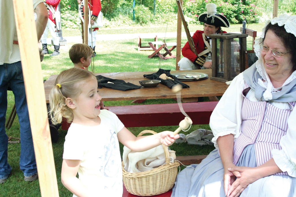 NOT SO EASY: Four-year-old Sadie Haugh tries her hardest to complete a traditional colonial game as Sgt. Denise Foggo of the Pawtuxet Rangers looks on and provides encouragement.
