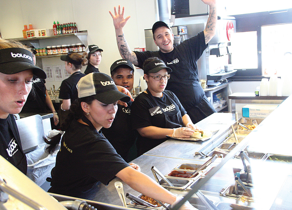 From the kitchen, those preparing burritos give an enthusiastic wave.