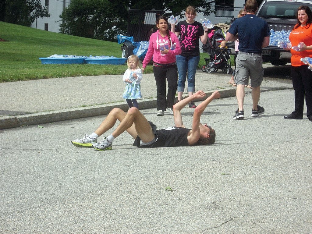 Raised in CELEBRATION:  The race's first finisher falls to the ground and raises his fists in both exhaustion and glory.