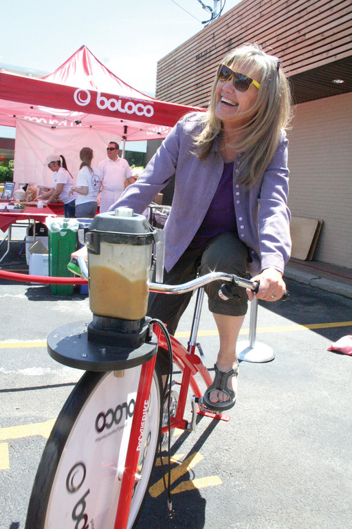 Visitors got to help make their own mango passion smoothies, as Cindy Bretter of Seattle did, by spinning a mixer powered by a stationary bicycle.