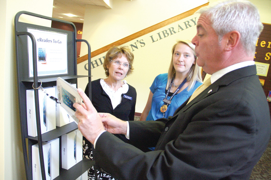 18 BOOKS ALL AT ONCE: Mayor Scott Avedisian checks out the display of iPads on loan at the Warwick Public Library. Looking on are library director Diane Greenwald and public service manager Jana Stevenson.