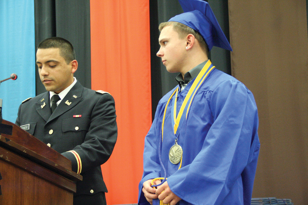 CREATIVE CAP, ARTISTIC IN THE MONEY: Warwick Veterans salutatorian Johnathan Moore accepts a $65,000 scholarship for his choice to be involved in the University of Rhode Island ROTC