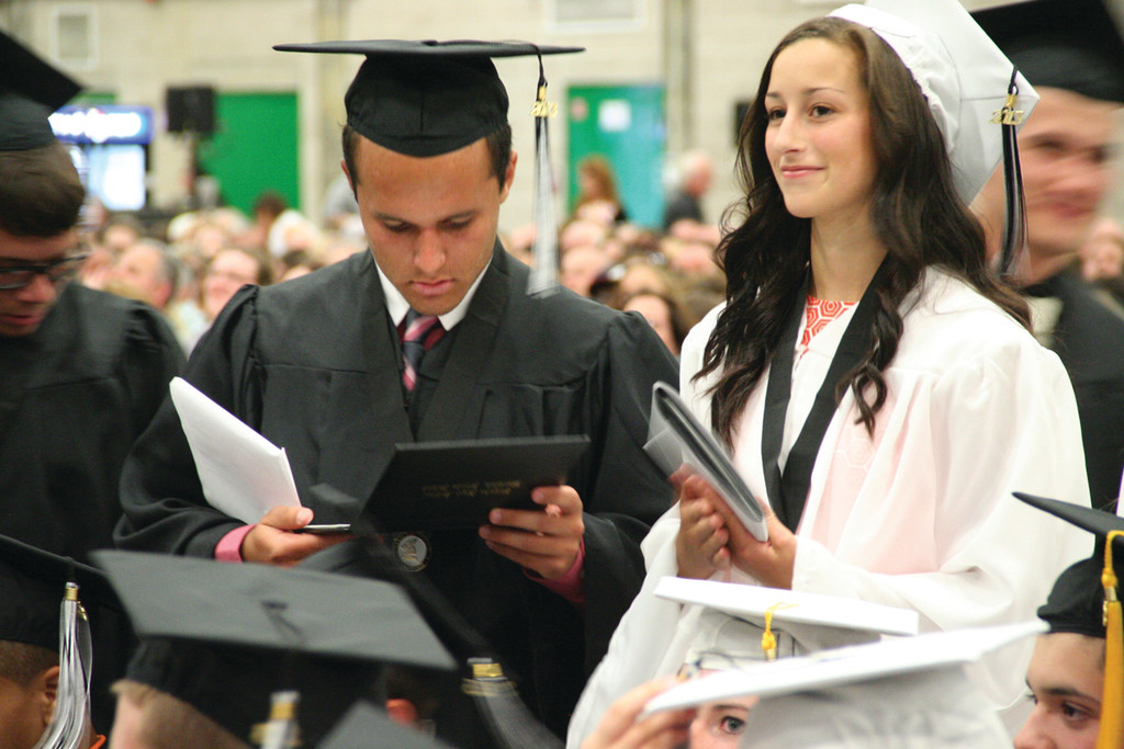Ryan Dean checks out his diploma while Talia D'Ambruoso cradles hers.