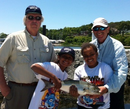 Take-a-Kid fishing big success: Taina and Zhiayre, both of Providence, RI with a blue fish they caught while fishing with Peter Sousa (left) of Warwick and Capt. Dave Monti during Saturday's Take-a-Kid fishing day sponsored by the RI Saltwater Anglers Association. This year 215 children participated.