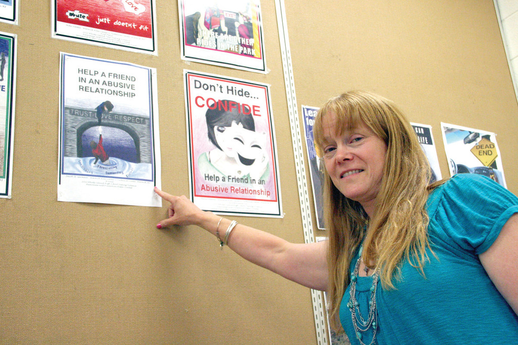 WINNING POSTER: Warwick Area Career and Technical Center graphic arts teacher Jann Gartner points to the two winning posters designed by her students in the Lindsay Ann Burke Memorial poster contest.
