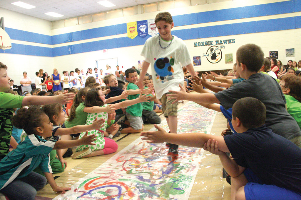 RUNWAY SENSATION: Sixth grade Hoxsie student Sam Passarelli hi-fives his peers showing off his Wassily Kandinsky design art T-shirt at the school's fashion/art show Tuesday.