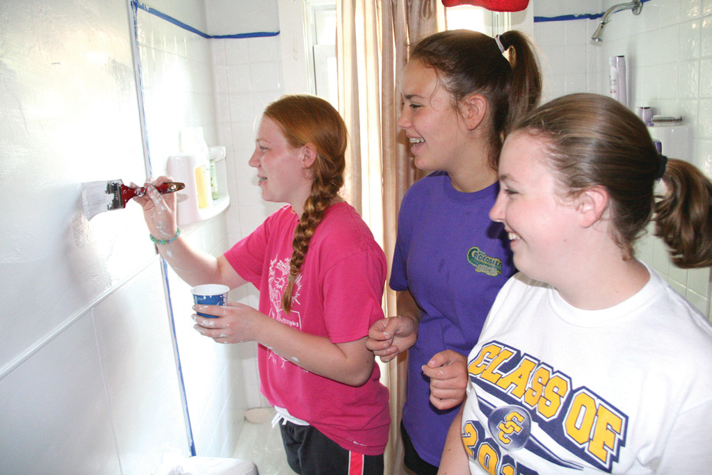 BRUSH UP: Volunteer teens Jen Ahearn, Kelly Angell and Cara Brown painted the bathroom in the home belonging to Joanne Devine.