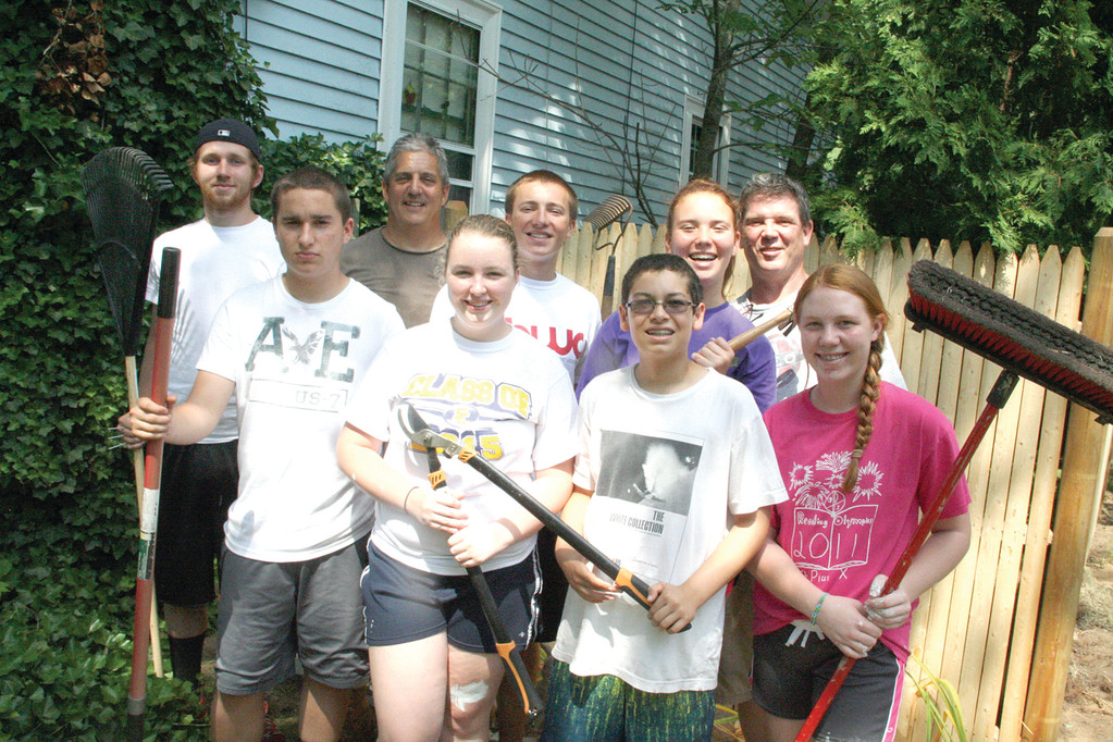 CLEANUP GANG: Teens and their counselors take a break from yard work and painting for this group shot in front of the Atlantic Avenue property they worked on yesterday.