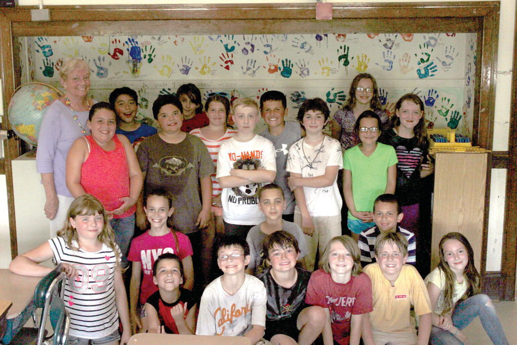 CLASS ACT: Whittaker and her fourth grade class pose with her on the last day of school in front of a mural of handprints made by students who have had Whittaker as a teacher through the years.