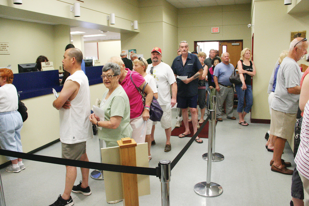 ALREADY A LINE: Most taxpayers received their motor vehicle on Friday and by Monday morning there was a line at the City Hall Annex. People were able to squeeze into the air-conditioned building to avoid the hot sun.