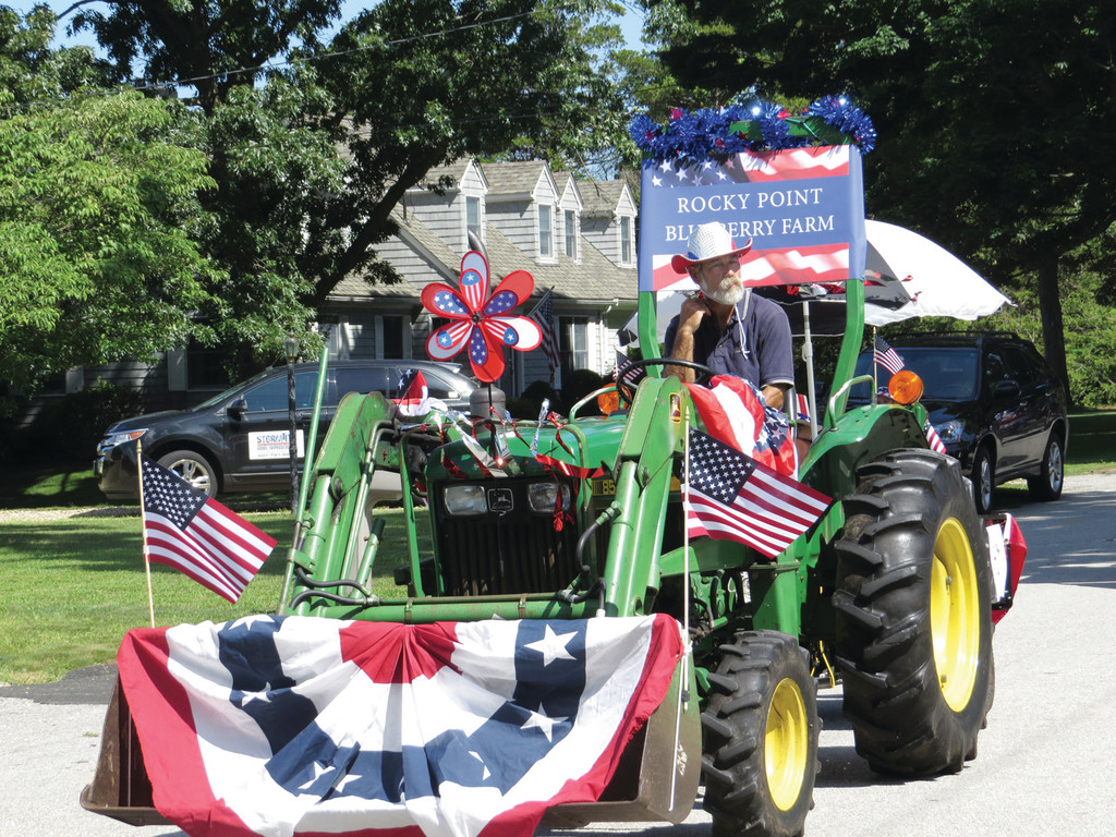 TRACTORS ON PARADE: The Rocky Point Blueberry Farm, which opened over the holiday weekend, joined in on the celebration by bringing their tractor along the parade route.