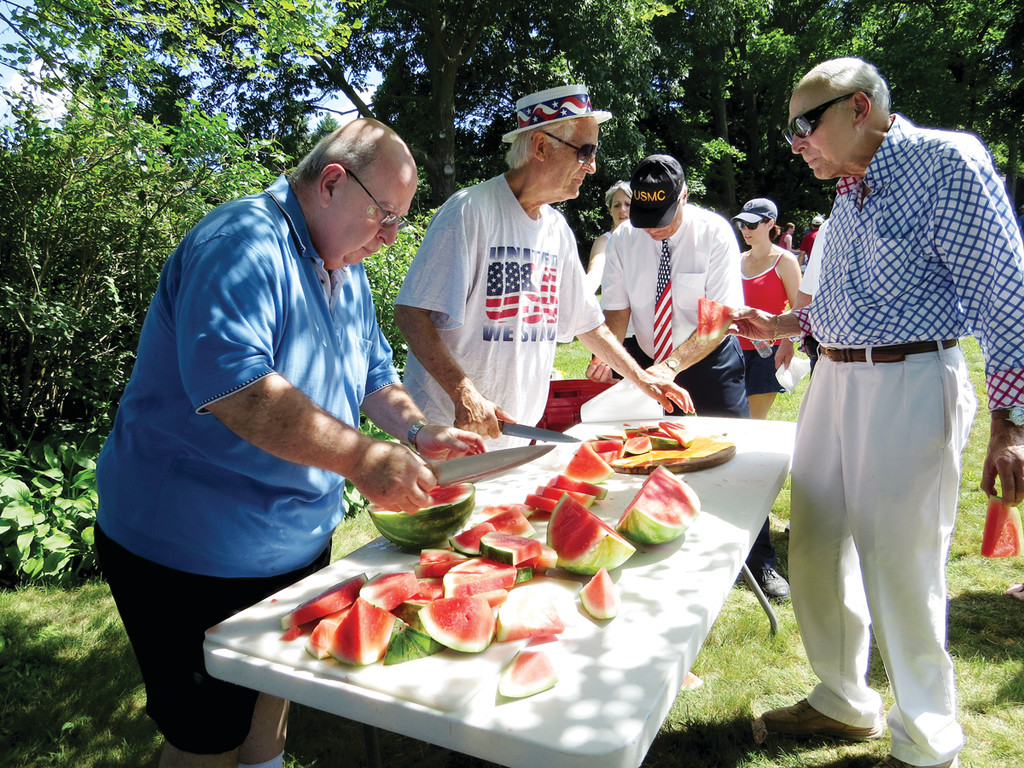 WATERMELON PROS: Shelly Nevins and Jack Henriques, two members of the Warwick Neck Improvement Association that sponsors the annual parade, were in charge of cutting the 14 watermelons to serve close to 200 people. Lemonade and cookies were also served.