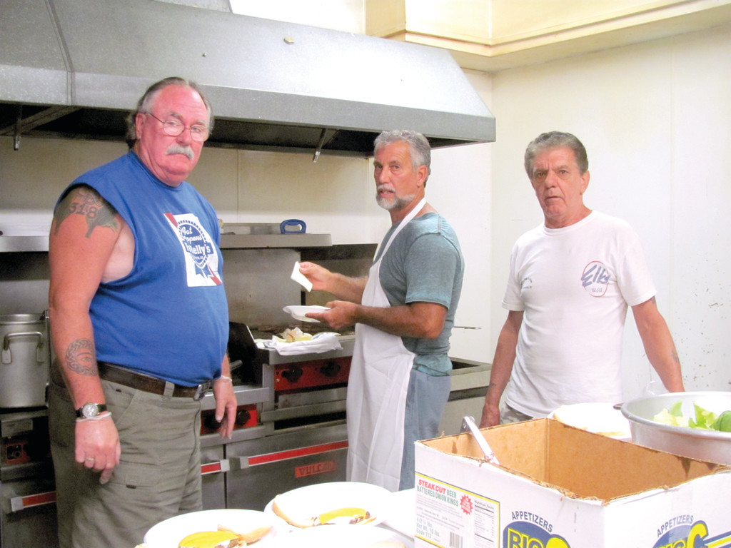 MASTER CHEF: Mark Eaton (center), Tri-City Elks Lodge No. 14's Exalter Ruler, takes a break from his chef duties during Tuesday's luncheon. Eaton cooked hot dogs, hamburgers and French fries for 60 veterans. Eaton was assisted by Ernie Battey (left) and Nick Rossi (right).