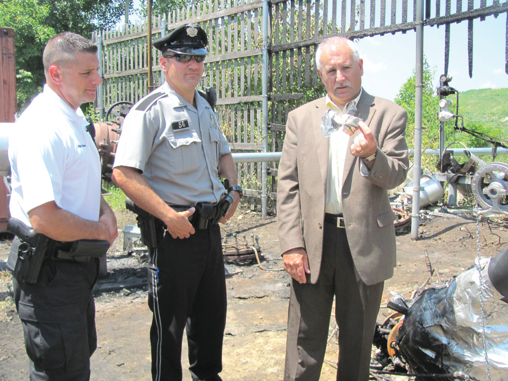 "Mayor Joseph Polisena, accompanied by Johnston Police Patrolman Chuck Psilopoulos and Patrolman Luca Lancelotti inside the plant, peeled a piece of duct tape off one of two Caterpillar ""Cat"" generators that were working without authorization from the town."