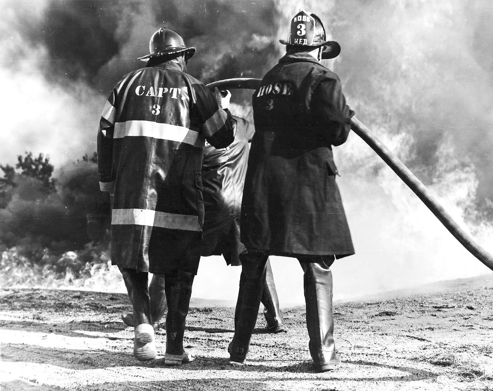 GET THE WATER: In this undated photo, members of the Oakland Beach Volunteer Fire Company fight a roaring blaze.