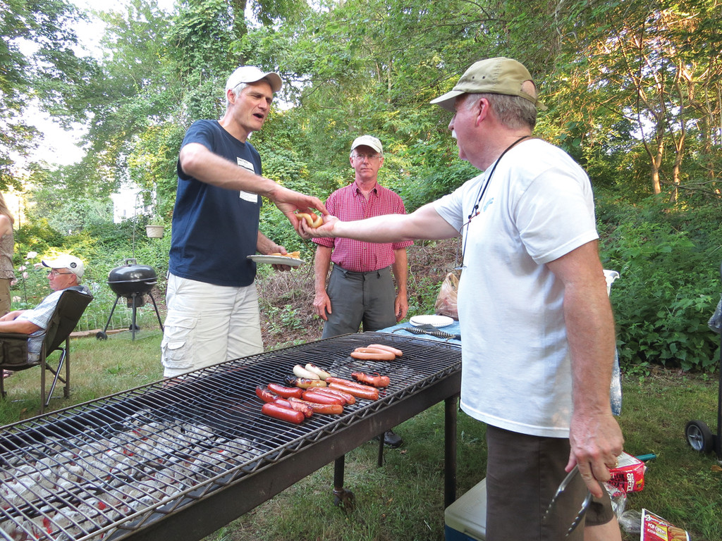 "HOT DOGS FOR EVERYONE: Armed with hot dogs from four states and almost 160 buns, Ken Proudfoot hosted not only his 23 family members, but his wife's family and their neighbors for a ""Hot Dog Throwdown."" Above, Ken, a former hot dog cart owner, serves his neighbor Jay David, as his brother David Proudfoot looks on."