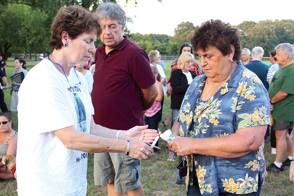 FLAMES OF HOPE: Fay's sister-in-law Sheila lights Barbara Corcoran's candle. Corcoran is Fay's former neighbor, and described him as quiet, kind and considerate. She hopes whoever is responsible for his death is apprehended soon.